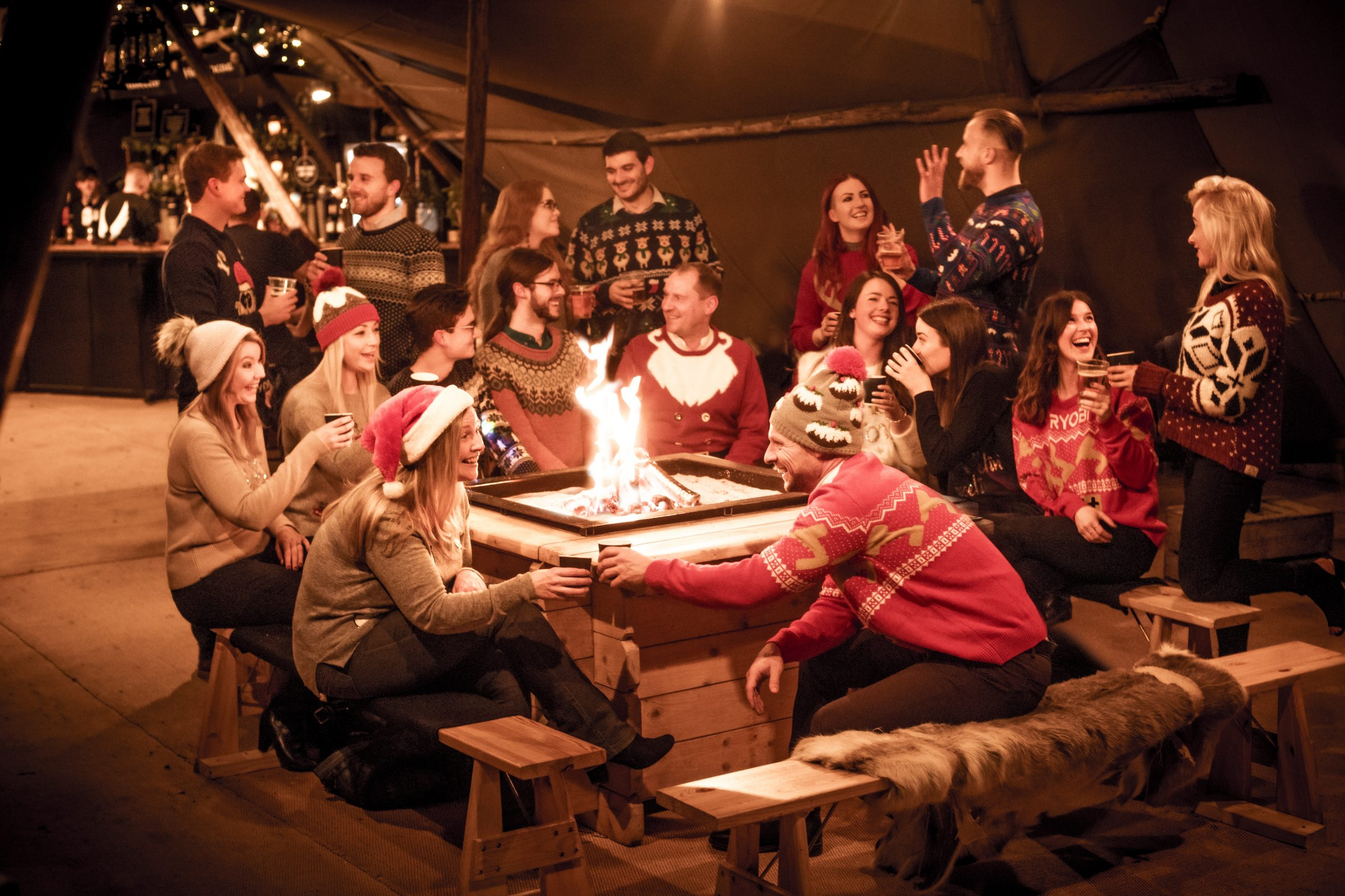 The Staff of We Are Boutique Gathered Around a Fire Wearing Christmas Jumpers