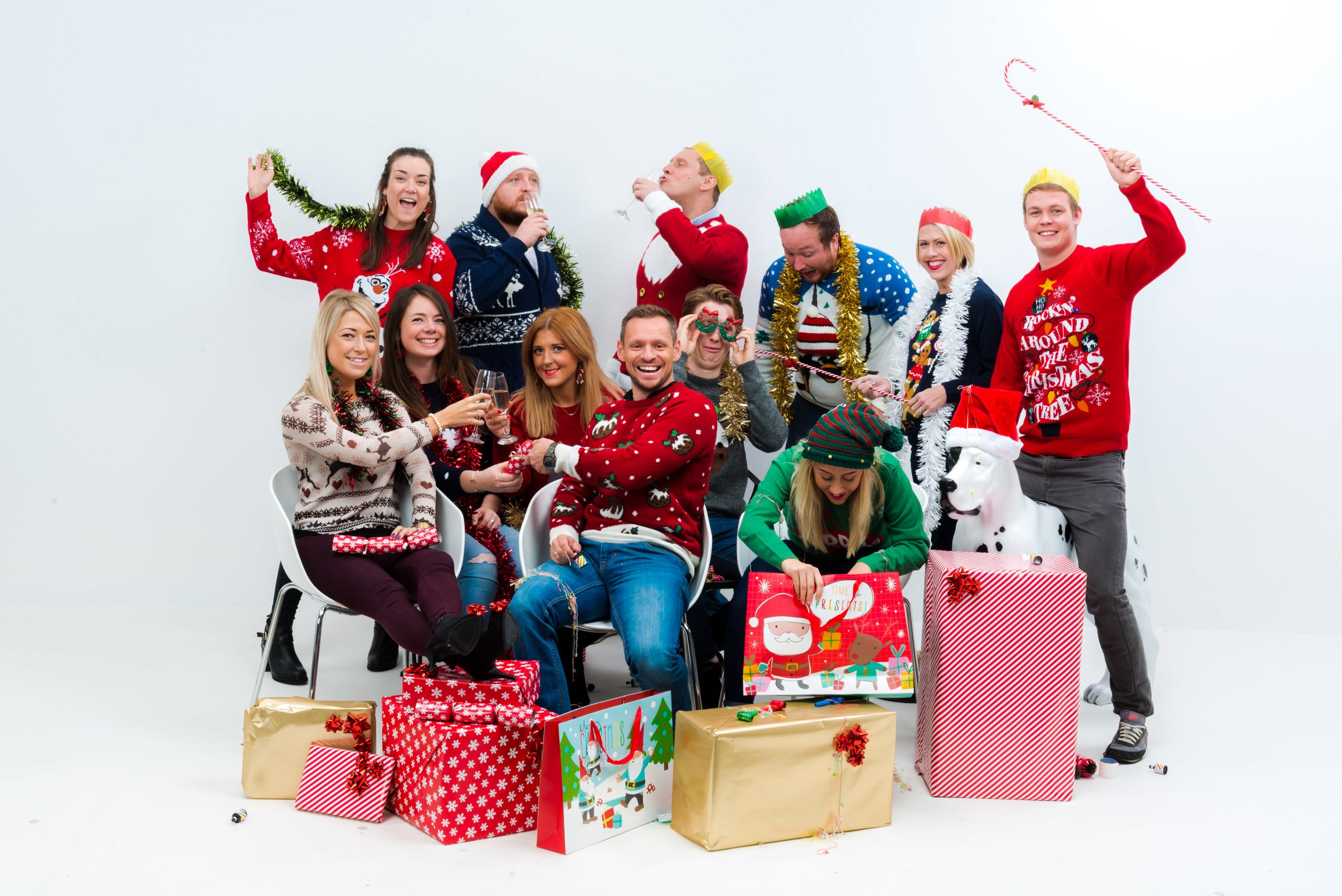 The staff of We Are Boutique looking joyus in christmas jumpers opening presents
