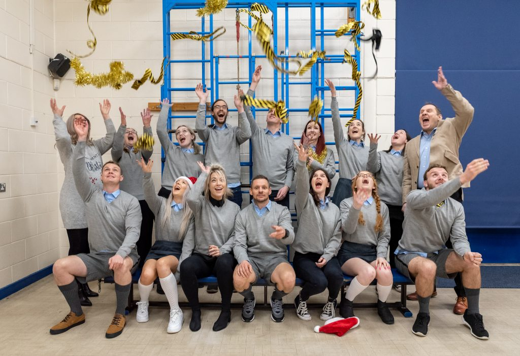 The Staff of We Are Boutique dressed up as School Children, throwing their ties in the air, looking joyous.